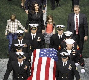 Taya Kyle (rear) and her children walk behind the coffin of her slain husband former Navy SEAL Chris Kyle during a memorial service for the former sniper at Cowboys Stadium in Arlington, Texas, February 11, 2013. Kyle was shot and killed with another man at a Texas gun range on February 2. REUTERS/Tim Sharp (UNITED STATES - Tags: CRIME LAW MILITARY OBITUARY)